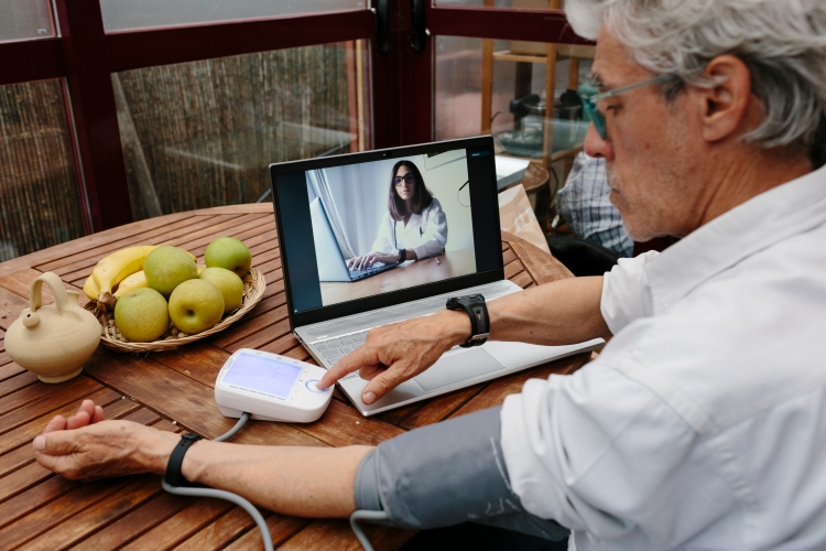 Elderly man checking his blood pressure at home in front of his laptop. He's having a video-chat with a female doctor who looks at him on the screen.