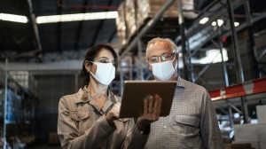Face-mask wearing colleagues in a warehouse