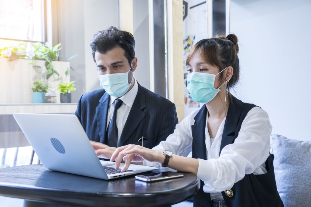 2 workers meeting together with laptop and wear protective masks